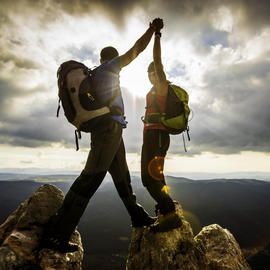 two people high-fiving on a mountain